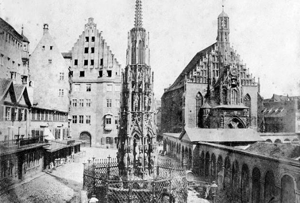 Der Schöne Brunnen von Westen mit der Frauenkirche im Hintergrund, dazwischen drängen sich die 1895 abgebrochenen Hauptmarkt-Kolonnaden. Um den Brunnen herum beleben gezeichnete Figuren die Architektur-Szenerie. (Stadtarchiv Nürnberg A 47-II-KS-134-23)